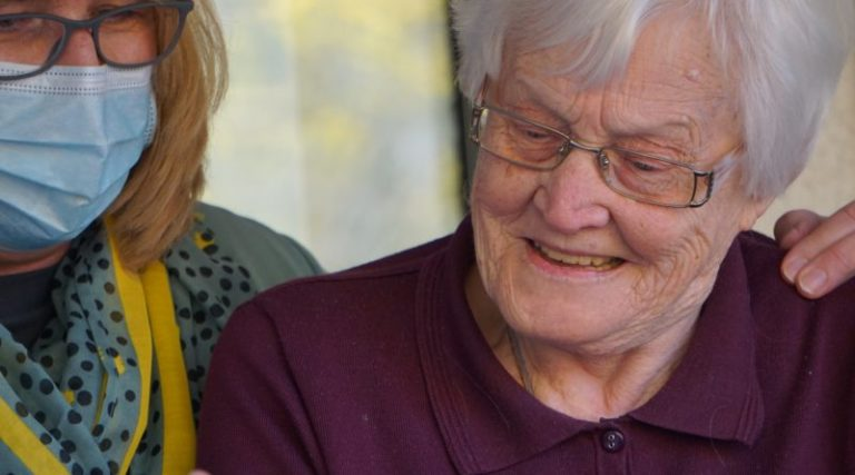 A masked carer looking after an Australian senior.