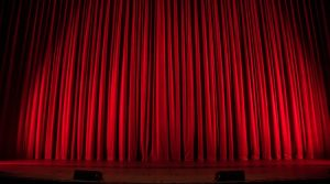 Red theatre curtain closed on a stage.