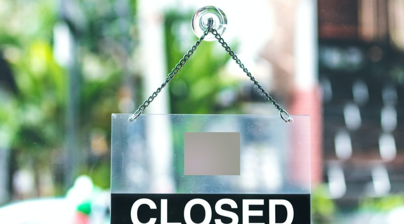 A closed sign hanging in a shop door.