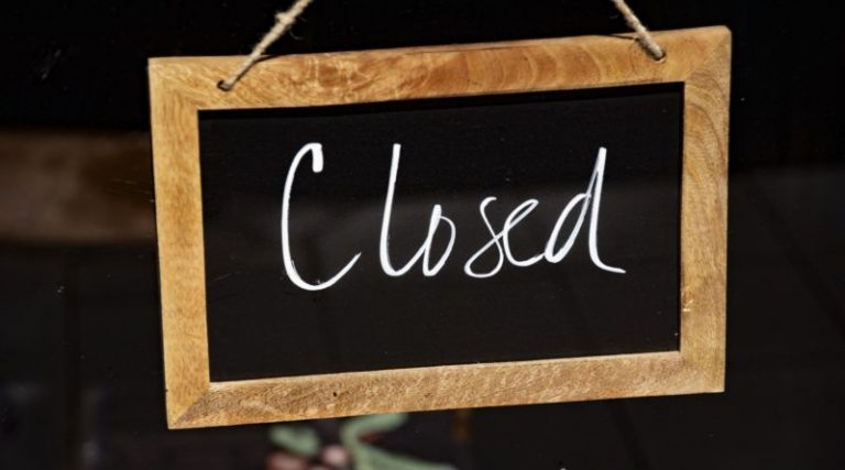 A closed sign hanging in a shop window