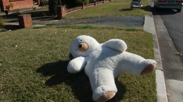 An old teddy bear left on the curb for collect
