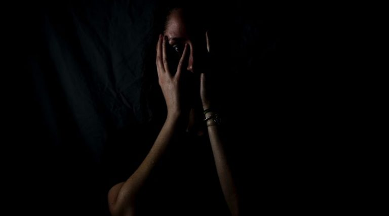 Woman in the dark holding her face