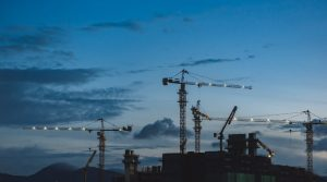 Skyline of construction cranes at night.