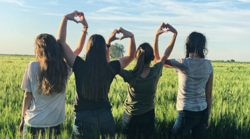 A group of young women making heart shapes with their hands.