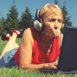 Senior woman laying on green grass, blowing a bubble with some bubble gum and listening to the radio on her laptop.