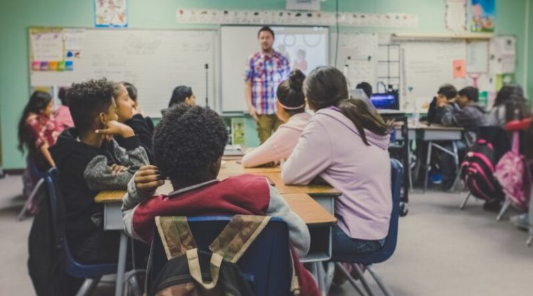 Classroom of kids looking forward towards their teacher