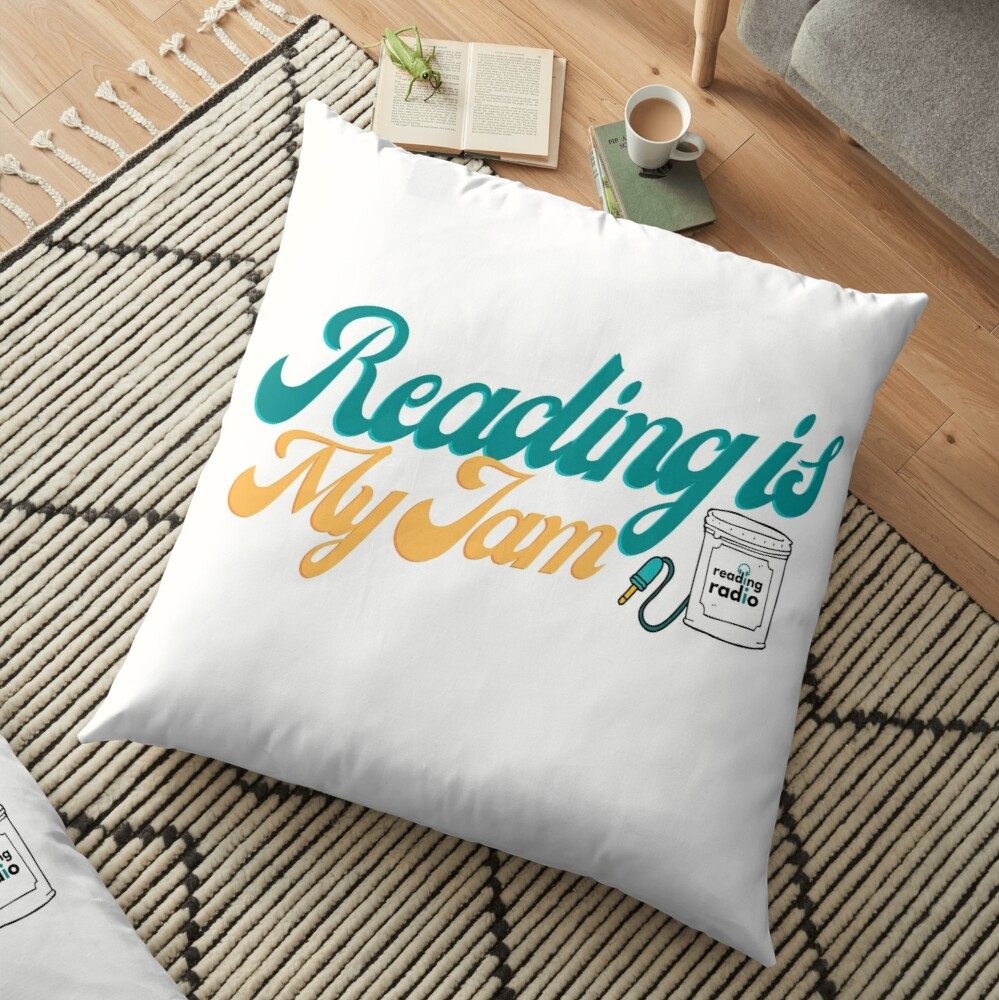 "White pillow on the carpet that reads ""Reading is my Jame"" with an Reading Radio logo on it."