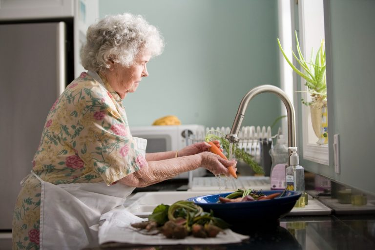 Elderly female washing the dishes
