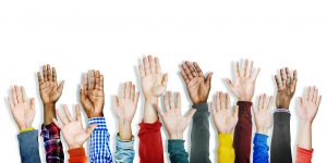 diverse hands in the air to volunteer