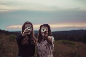 Two girls holding two flowers